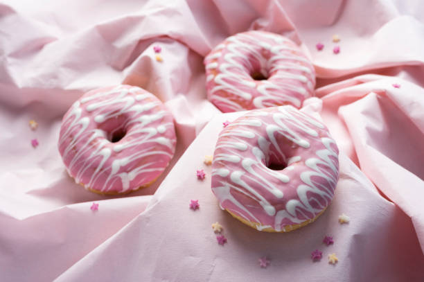 Pink glaze decorated donuts on wavy pink background in various focus stock photo