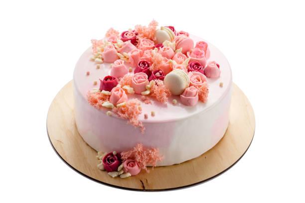 rosa glasierte kuchen mit creme blumen isoliert auf weiss - rosentorte stock-fotos und bilder