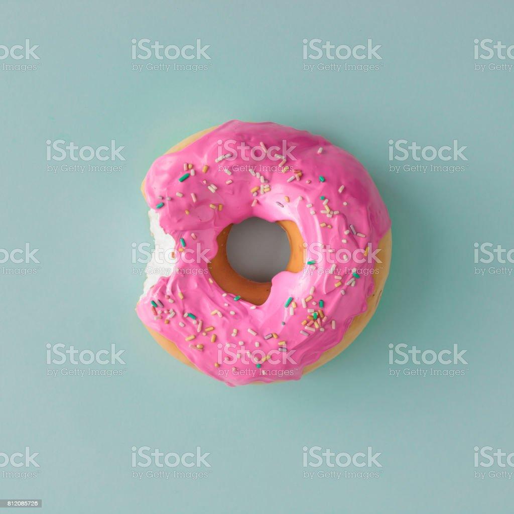 Pink glazed donut on blue pastel background. Flat lay. Creative concept. stock photo