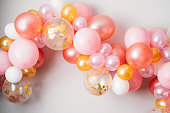 Pink golden balloon garland\nFestive decoration hanging on the wall