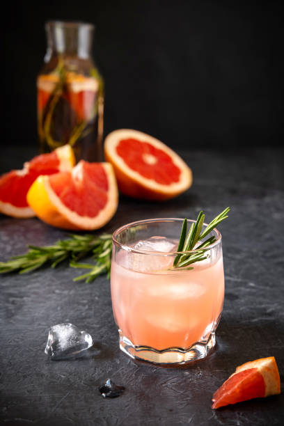 Pink Grapefruit Cocktail Spritze With Rosemary And Melting Ice Pink Grapefruit Cocktail Spritze With Rosemary And Melting Ice spritze stock pictures, royalty-free photos & images