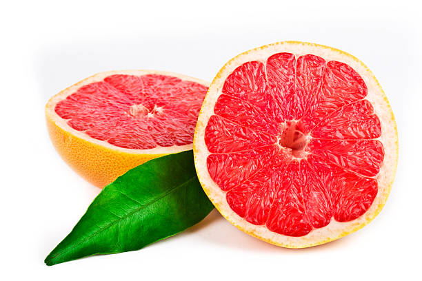 Pink grapefruit cut in half with a green leaf stock photo