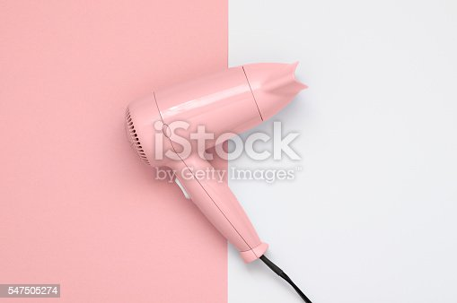 Pink hair dryer on pink and white paper background