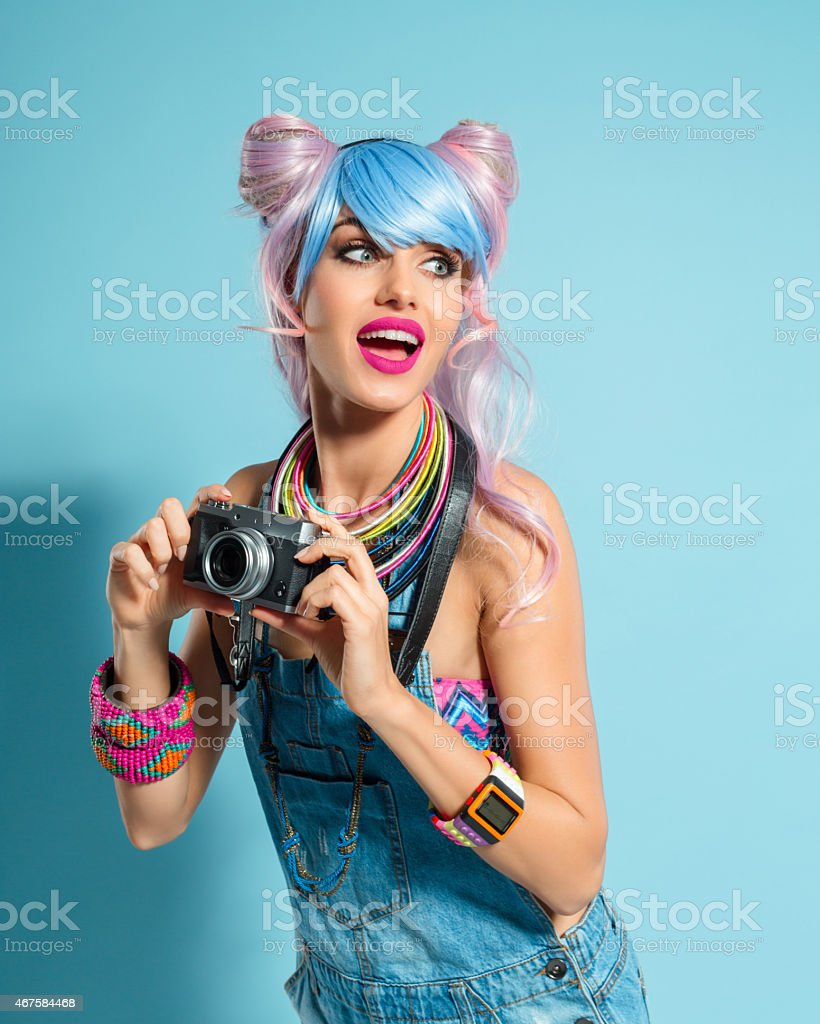 Pink hair girl in funky manga outfit holding camera Portrait of surprised manga style pink hair young woman wearing denim coveralls, holding camera in hands. Standing against blue background. Studio shot, one person. 2015 Stock Photo