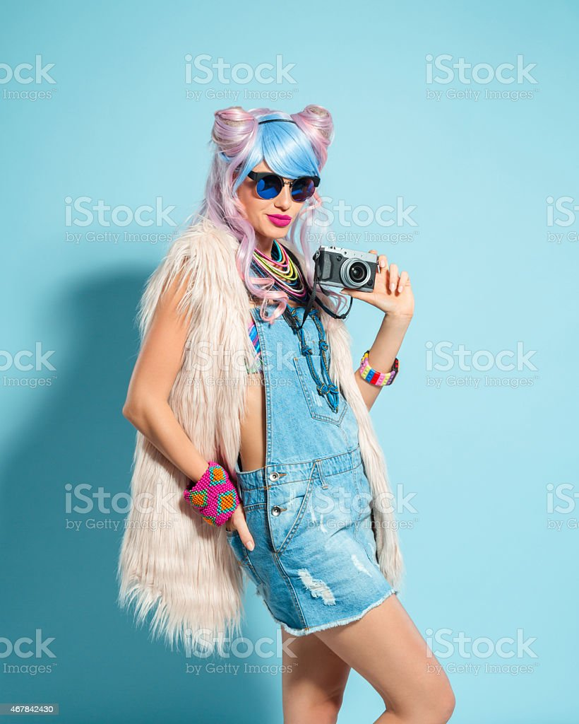 Pink hair girl in funky manga outfit holding camera Portrait of sensual manga style pink hair young woman wearing denim coveralls, fur vest and sunglesses. Standing against blue background, holding camera in hands and looking at camera. Studio shot, one person. 2015 Stock Photo