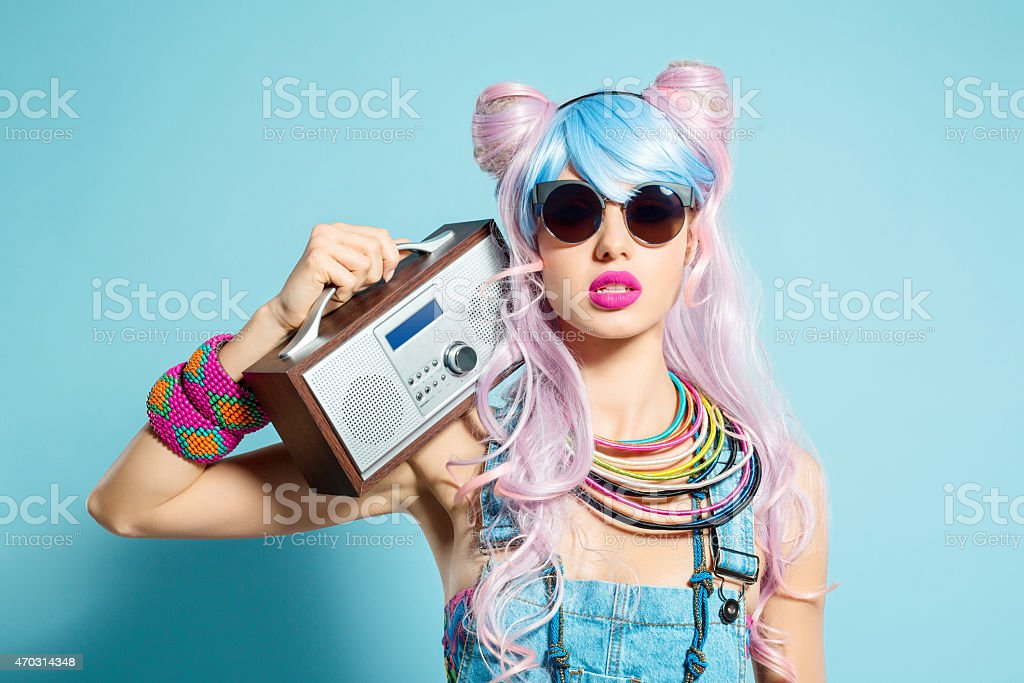 Pink hair girl in funky manga outfit holding radio royalty-free stock photo