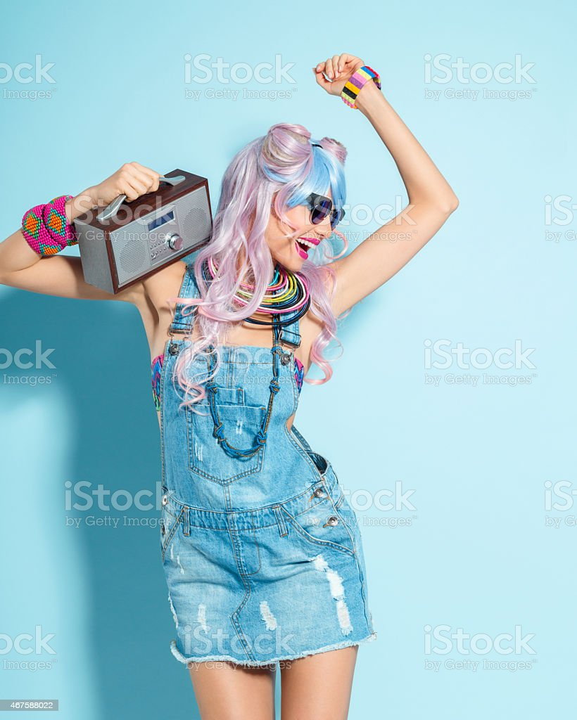 Pink hair girl in funky manga outfit holding small radio Portrait of cheerful manga style pink hair young woman wearing denim coveralls. Standing against blue background, holding small radio on her shoulder, listening to the music and dancing. Studio shot, one person. 2015 Stock Photo
