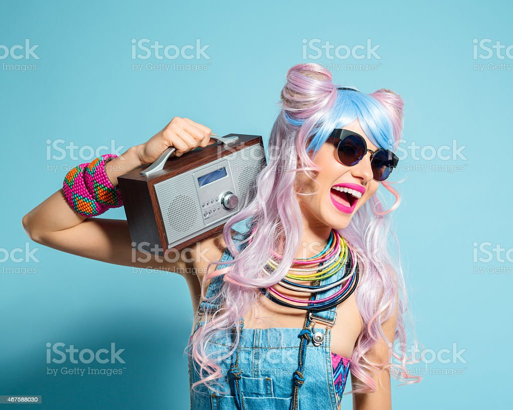 Pink hair girl in funky manga outfit holding small radio - Royalty-free 2015 Stock Photo