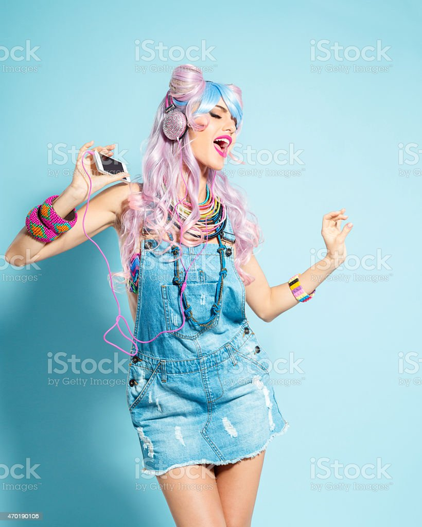 Pink hair girl in funky manga outfit listening to mp3 stock photo