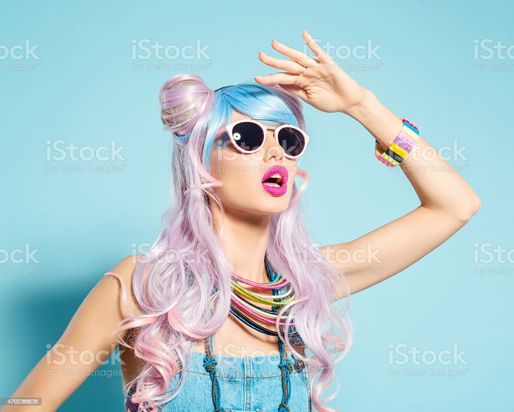 Pink hair girl in funky manga outfit Portrait of sensual manga style blue-pink hair young woman wearing denim coveralls and sunglasses. Standing against blue background, looking away with raised hand. Studio shot, one person. 2015 Stock Photo