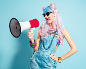 Portrait of happy manga style blue-pink hair young woman wearing denim coveralls, shpouting into megaphone. Standing against turquoise background. Studio shot, one person.