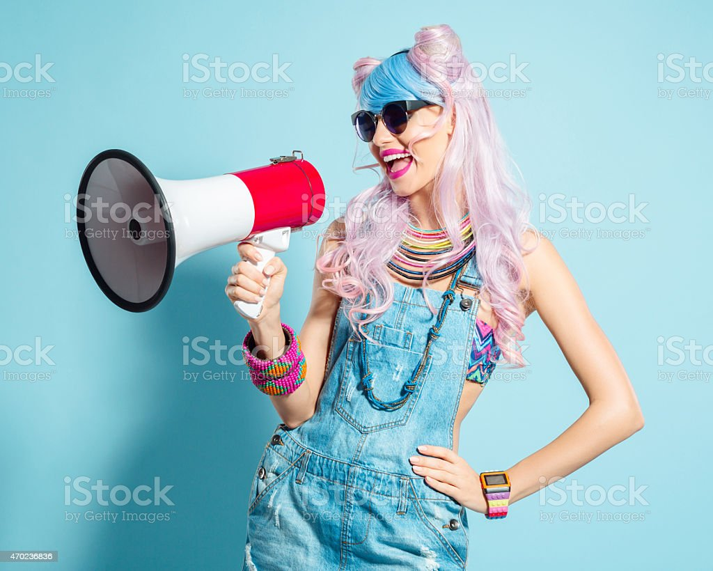 Pink hair girl in funky manga outfit screaming into megaphone stock photo