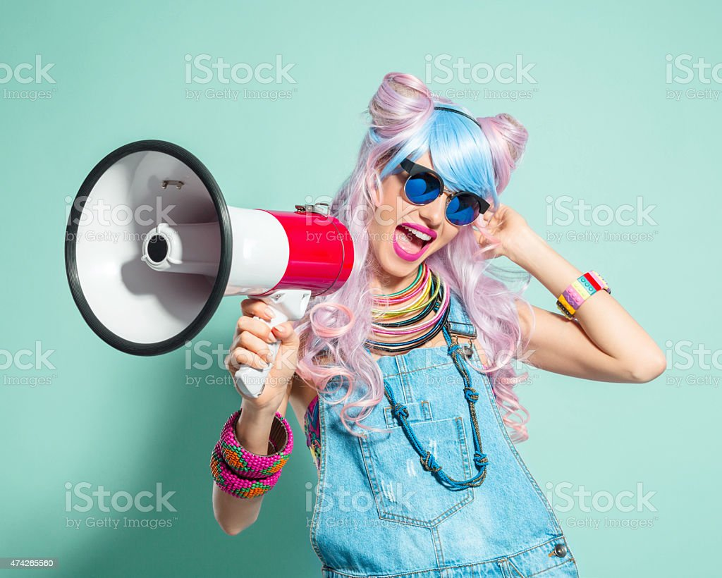 Pink hair girl in funky manga outfit screaming into megaphone - Royalty-free 2015 Stock Photo
