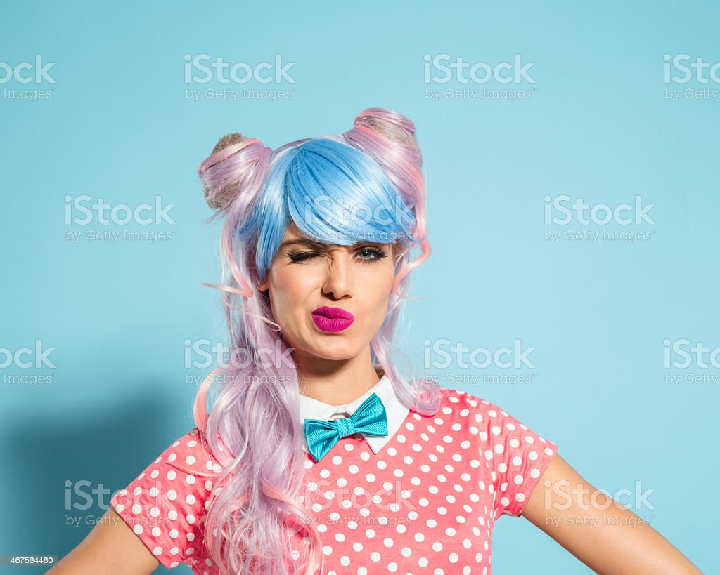 Pink hair manga style girl grimacing Portrait of confident manga style blue-pink hair girl wearing pink polka dot dress with collar and bow tie. Standing against blue background, looking at camera. Studio shot, one person. 2015 Stock Photo
