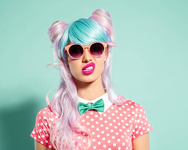 Pink hair manga style girl grimacing Portrait of manga style blue-pink hair girl wearing sunglasses and pink polka dot dress with collar and bow tie. Standing against turquoise background, looking at camera. Studio shot, one person. funky stock pictures, royalty-free photos & images
