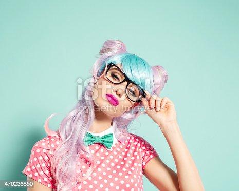 istock Pink hair manga style girl holding nerd glasses 470236850