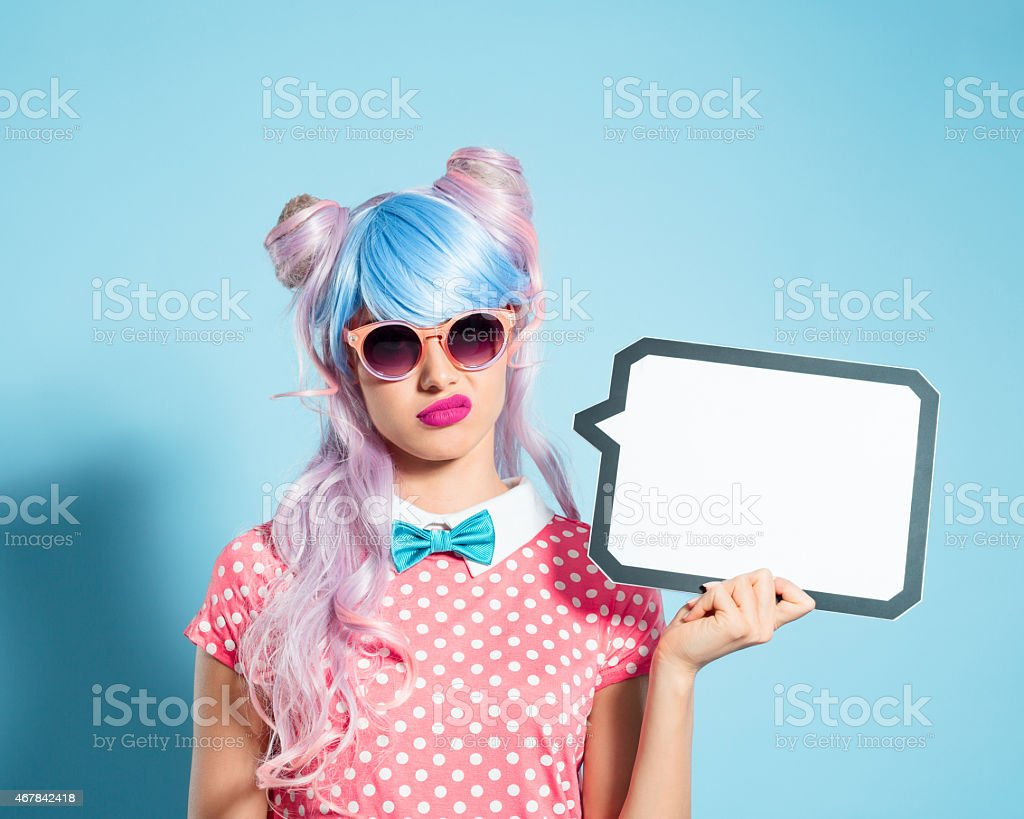 Pink hair manga style girl holding speech bubble Portrait of grimacing manga style blue-pink hair girl wearing sunglasses and pink polka dot dress with collar and bow tie. Standing against blue background, holding a speech bubble in hand. Studio shot, one person. 2015 Stock Photo