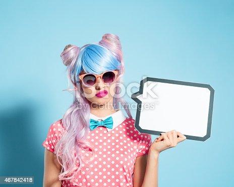 istock Pink hair manga style girl holding speech bubble 467842418