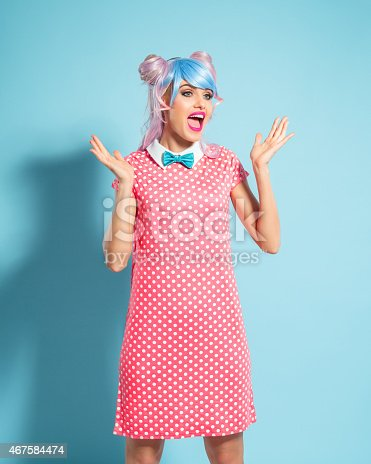 Portrait of cheerful manga style blue-pink hair young woman wearing pink polka dot dress with collar and bow tie. Shouting with raised hands against blue background. Studio shot, one person.