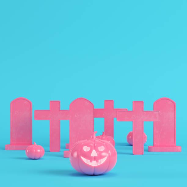 halloween-kürbisse mit kreuzen und grabsteinen auf leuchtend blauem hintergrund in pastellfarben rosa. minimalismus konzept - halloween grabsteine stock-fotos und bilder