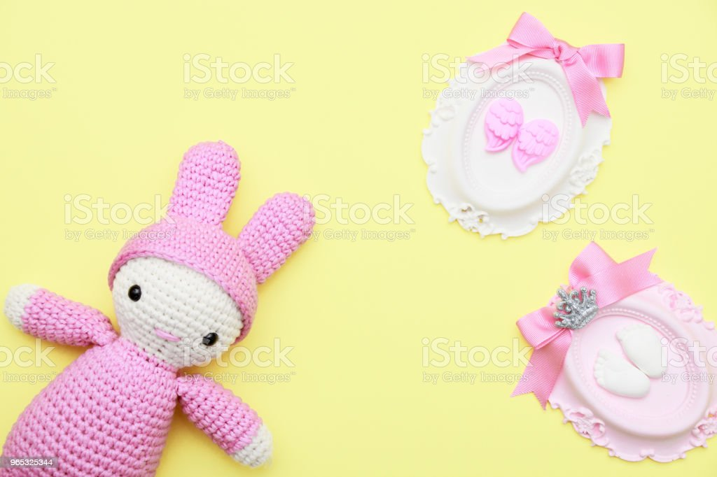 Pink hand made baby toy and babyshower stone has angel wing, foot, ribbons on yellow flat lay zbiór zdjęć royalty-free