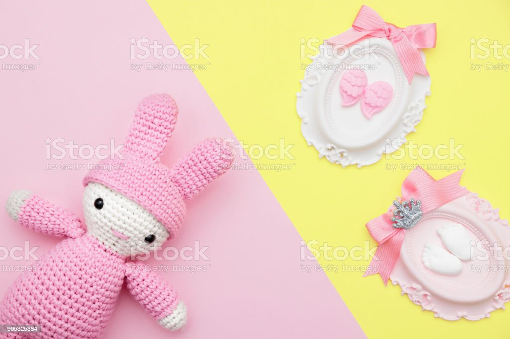 Pink hand made baby toy and babyshower stone has angel wing, foot, ribbons on yellow flat lay royalty-free stock photo