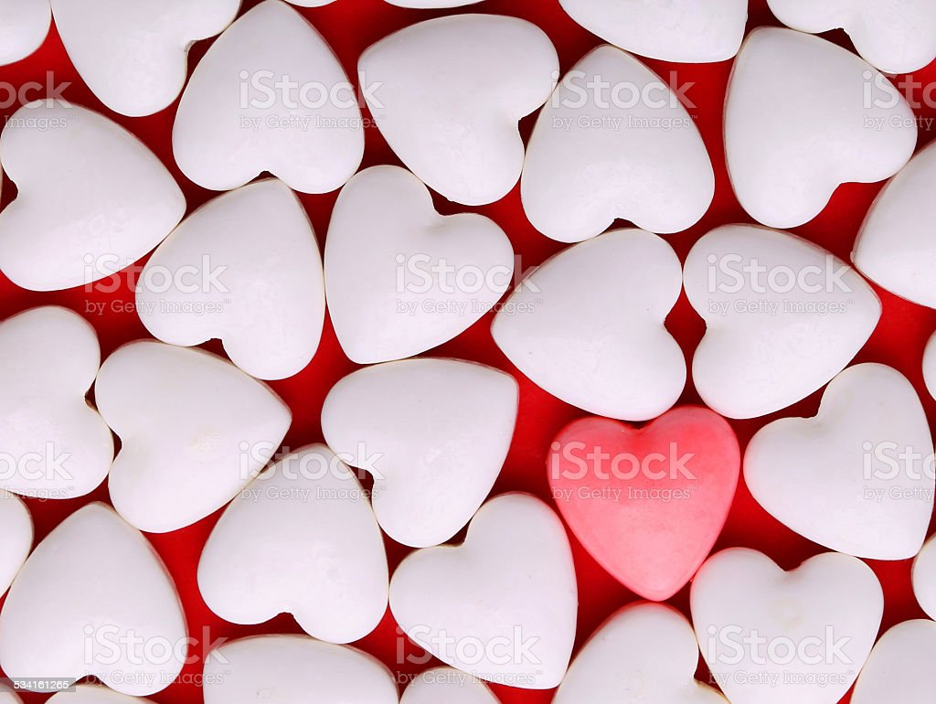 Pink heart between pile of white hearts. Candy Hearts background stock photo