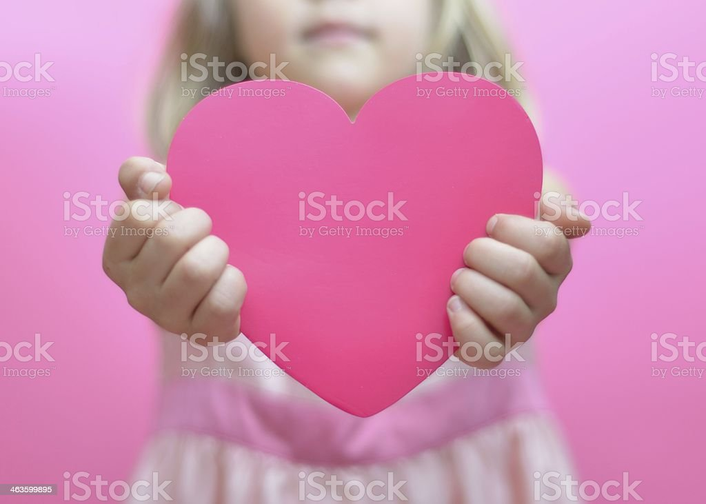 Pink heart held by little girl stock photo