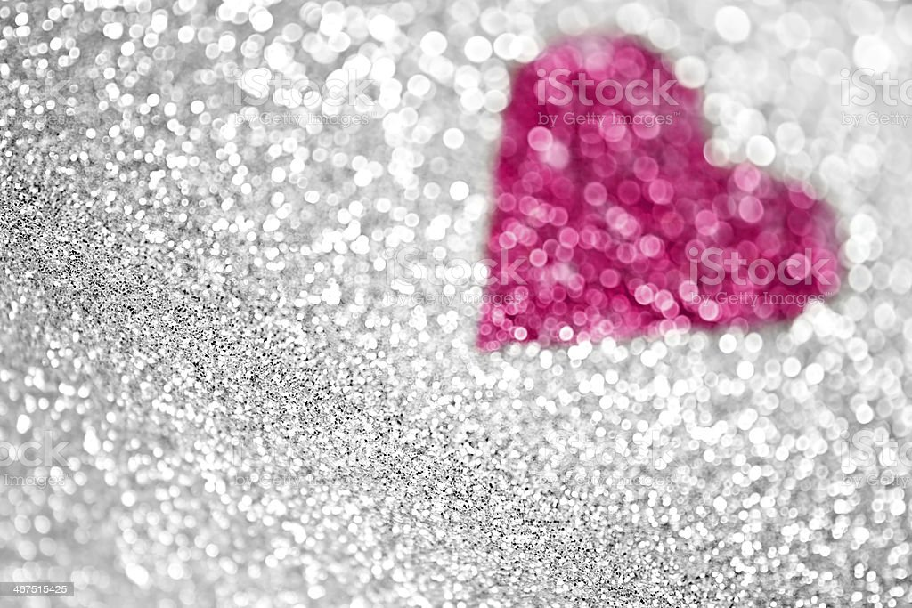 pink heart made of glitter in a silver glitter background royalty free stock photo
