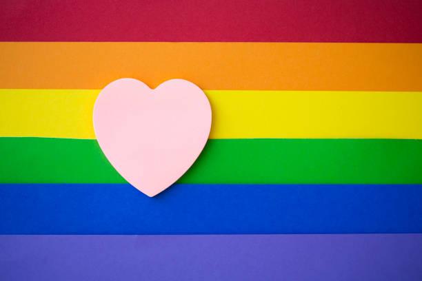 corazón de color rosa sobre fondo arco iris - intergénero fotografías e imágenes de stock