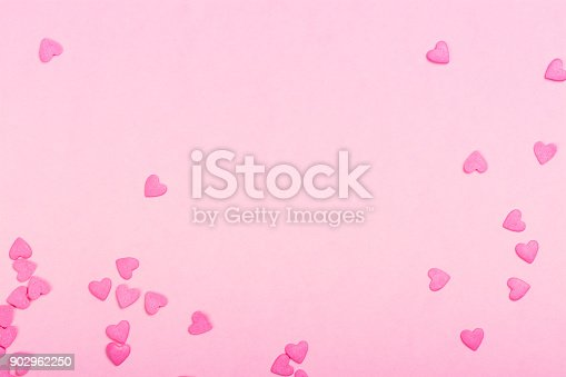 istock Pink heart shaped sprinkles on pink Valentines day background 902962250