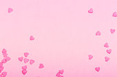 Pink heart shaped sprinkles on pink Valentines day background. Copy space