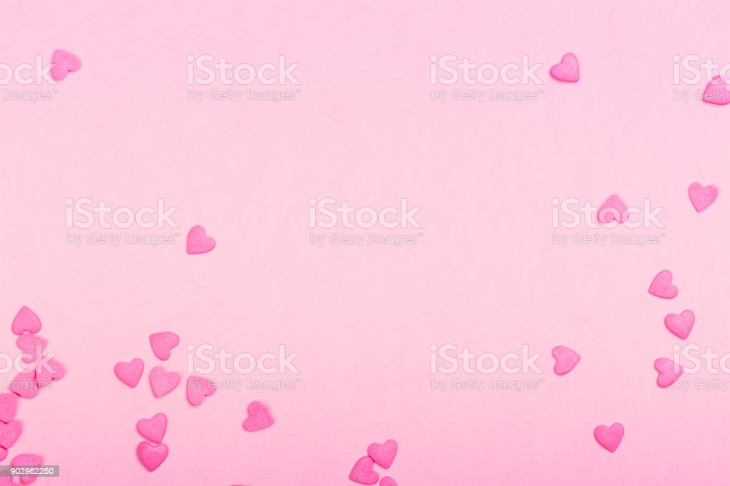 Pink heart shaped sprinkles on pink Valentines day background stock photo