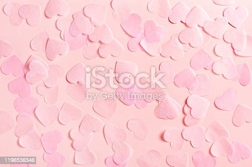 Pink hearts made of paper on a pink background, top view. Delicate pastel pink background with hearts for Valentine's day or wedding. Love and romance