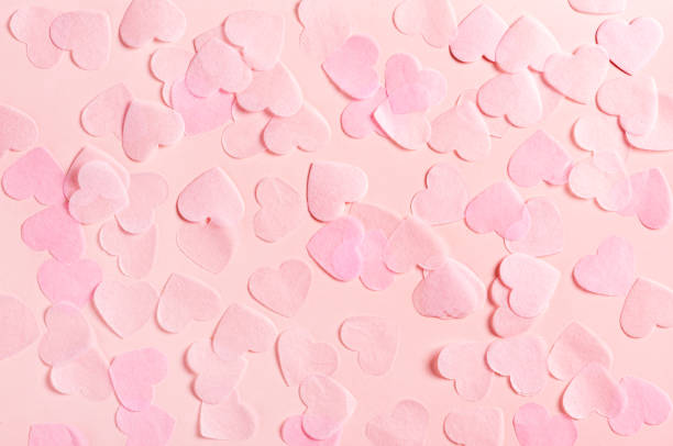pink hearts made of paper on a pink background, top view - valentines day стоковые фото и изображения