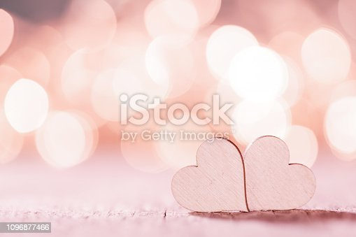 Two small handmade pink wooden hearts on bright lights bokeh background