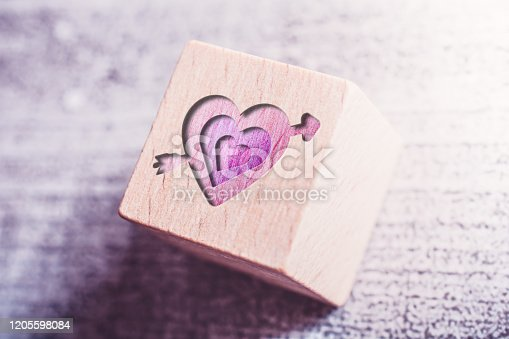 970844120 istock photo 3 Pink Hearts Pierced By A Cupid Arrow Engraved On A Wooden Block On A Table 1205598084