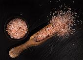 Pink Himalayan coarse grain salt on black stone background