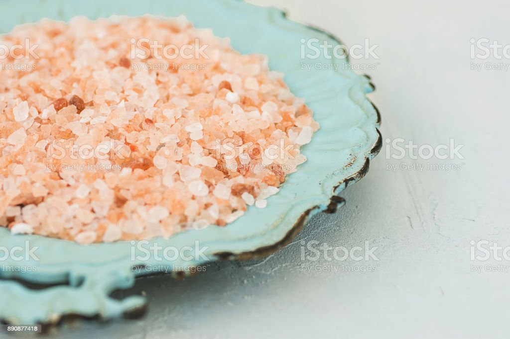 Pink Himalayan Salt on Vintage Turquoise Plate White Stone Tabletop Wellness Spa Healthy Diet Nutrition Ayurveda Clean Minimalist Image Copy Space stock photo