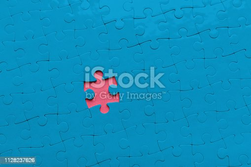 Individuality and hidden inclinations concept. Pink hole in blue puzzle background, copy space