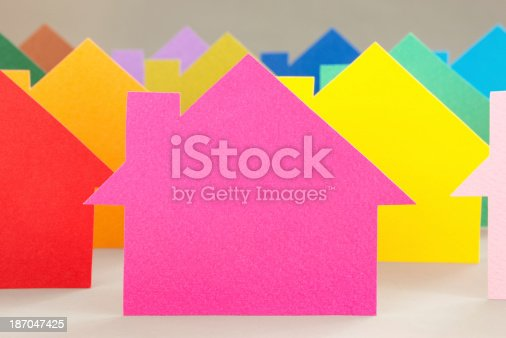 Group of colorful paper model houses with one pink in focus for real estate development concept