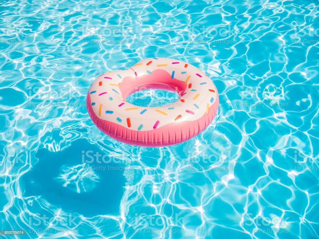 Pink inflatable donut swimming ring in a swimming pool stock photo