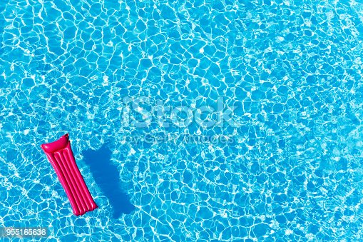 High angle view of empty pink inflatable mattress floating on blue water surface with copy-space