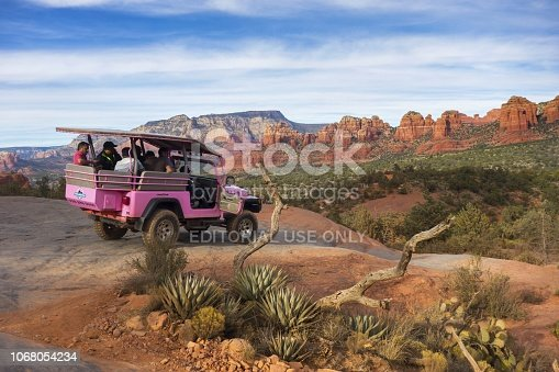 Sedona, Arizona, USA - December 10, 2017: Pink Jeep Off Road Terrain Vehicle touring Broken Arrow Slick Rock with Tourists on Vacation