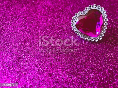 Pink heart jewelry on a glitter background.
