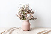 Beautiful floral arrangement including beautiful dried pink King Proteas and delicate thryptomene flowers, in a stylish pink vase, on a rustic table cloth.