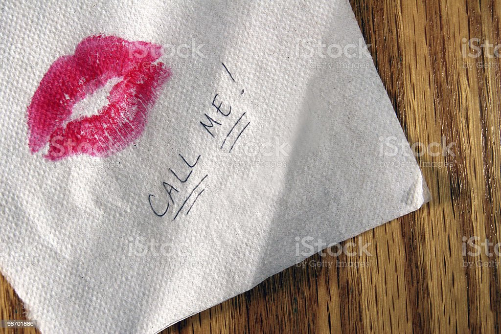 Pink kiss on a napkin with call me written on it stock photo