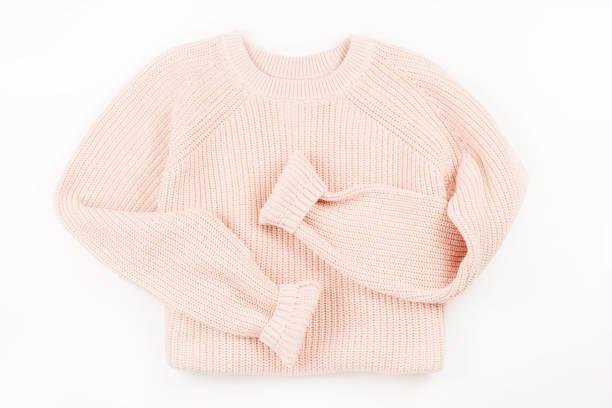 Pink knit sweater flat lay on white background. stock photo