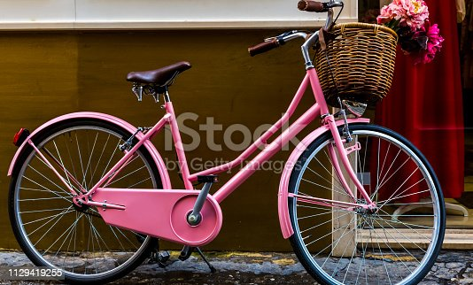 Pink ladies' bicycle with a basket stands against the wall.