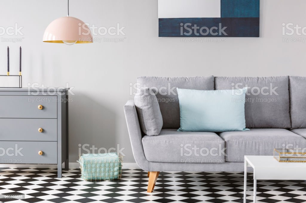 Pink Lamp Above Grey Cabinet Next To Sofa On Checkered Floor In Pastel Living Room Interior Real Photo Stock Photo Download Image Now Istock
